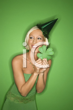 Royalty Free Photo of a Smiling Woman on Green Background Wearing a Party Hat and Holding a Shamrock for Saint Patrick's Day celebration.