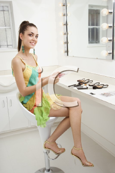 Royalty Free Photo of a Female Caucasian Applying Makeup While Looking at the Viewer and Smiling