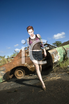 Royalty Free Photo of a Sexy tattooed Caucasian woman walking towards viewer seductively in junkyard