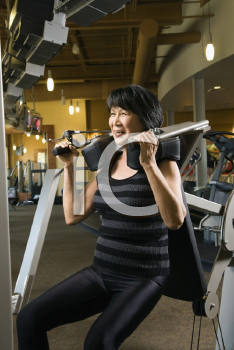 Royalty Free Photo of an Older Woman Using an Exercise Machine at a Gym