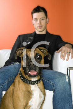 Royalty Free Photo of a Man Sitting With a Boxer Dog