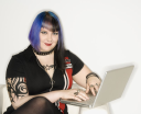 Royalty Free Photo of a Tattooed Woman With Blue Hair Typing on a Laptop