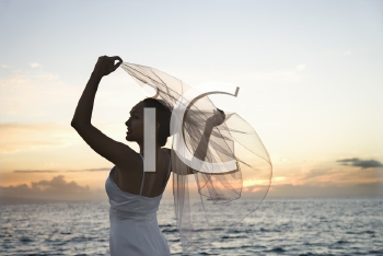 Royalty Free Photo of Young Bride Holding Out Her Veil on a Beach