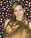 Royalty Free Photo of a Teen Girl Holding a Pomeranian Dog