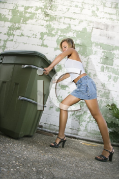 Royalty Free Photo of a Woman Wearing High Heels Pushing a Trash Can in an Alley