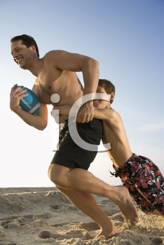 Royalty Free Photo of a Father Running With a Football Being Tackled by His Son