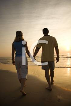Royalty Free Photo of a Couple Holding Hands and Walking Down the Beach at Sunset