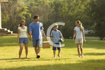 Royalty Free Photo of a Family of Four Walking in Park Carrying a Picnic Basket