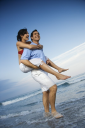 Royalty Free Photo of a Man Giving a Woman a Piggyback on the Beach