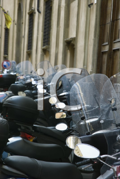 Royalty Free Photo of a Row of Motorcycles Beside a Building in Italy
