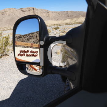 Royalty Free Photo of the Death Valley National Park Entrance Sign Reflected in the Side View Vehicle Mirror