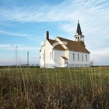 Royalty Free Photo of a Small Rural Church in a Field With Chipped Wood Siding
