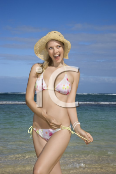 Mid-adult Caucasian female untying her bikini string with ocean in background.