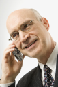 Smiling Caucasian middle-aged businessman talking on cellphone against white background.