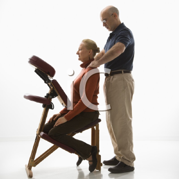Royalty Free Photo of a Massage Therapist Massaging the Back of a Woman Sitting in a Massage Chair