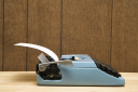 Royalty Free Photo of a Vintage Blue Typewriter on a Desk With Wood Paneling