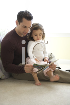Royalty Free Photo of a Father Reading a Book to His Daughter