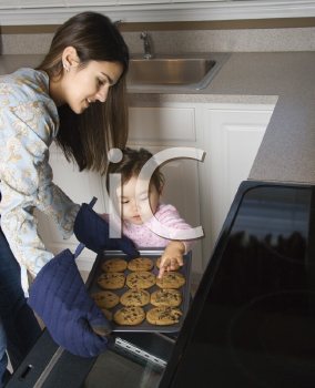 Royalty Free Photo of a Mother and Daughter Taking Cookies out of the Oven