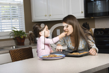 Royalty Free Photo of a Girl Feeding Her Mother Cookies