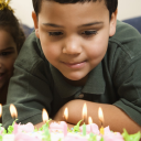 Royalty Free Photo of a Boy Looking Down Wishfully at Lit Candles of a Birthday Cake With Girl Peeking in Over His Shoulder
