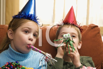 Royalty Free Photo of Children Looking Bored Wearing Party Hats and Blowing Noisemakers