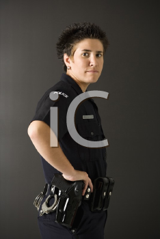 Royalty Free Photo of a Policewoman Standing With Her Hand on a Gun Holster