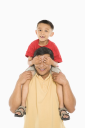 Royalty Free Photo of a Boy Sitting on His Father's Shoulders With Hands Over His Eyes