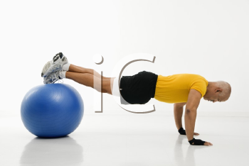 Royalty Free Photo of a Man Doing Pushups While Balancing on an Exercise Ball
