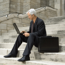 Royalty Free Photo of a Businessman Sitting on Steps Outdoors With a Laptop and Briefcase