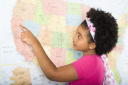 Royalty Free Photo of a Girl Pointing on a Map of the United States