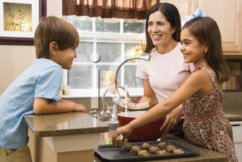 Royalty Free Photo of a Mother and Children Baking Cookies