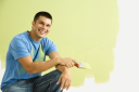 Royalty Free Photo of a Smiling Man Kneeling in Front of a Partially Painted Wall Holding a Paintbrush