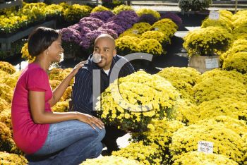 Royalty Free Photo of a Couple Picking Flowers at an Outdoor Plant Market