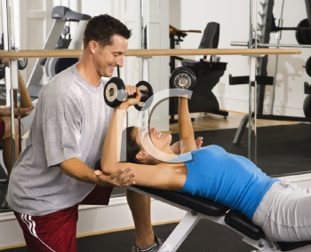 Royalty Free Photo of a Man Assisting a Woman Lifting Weights at a Gym
