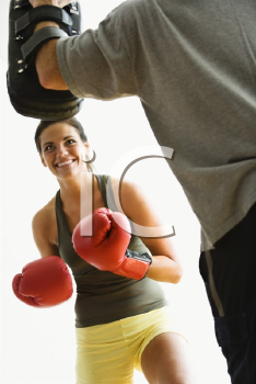 Royalty Free Photo of a Woman Wearing Boxing Gloves Hitting Training Mitts a Man is Holding
