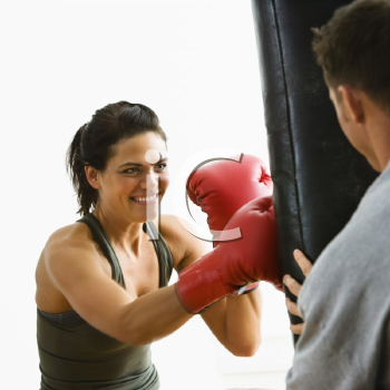Royalty Free Photo of a Female Boxing Hitting a Punching Bag