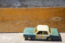Royalty Free Photo of a Toy Police Car on a Wooden Shelf