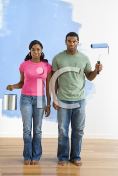 Royalty Free Photo of a Couple Standing Next to a Half-Painted Wall with Paint Supplies - American Gothic-Style