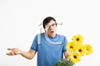 Royalty Free Photo of a Man Holding a Bouquet of Yellow Gerber Daisies Shrugging