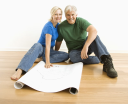 Royalty Free Photo of a Couple Sitting on the Floor with Architectural Blueprints