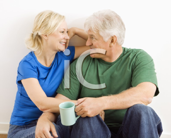 Middle-aged couple sitting together snuggling and drinking coffee.
