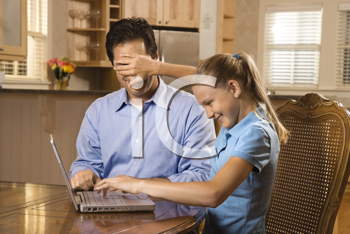 Young girl working on laptop at home covering man's face with hand.