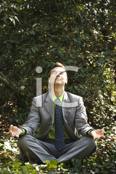 Young businessman sits in a lotus position meditating in the woods with closed eyes and a smile.