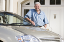 Royalty Free Photo of a Man Outside His House Beside a Car