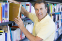 Royalty Free Photo of a Man Choosing a Book in a Library