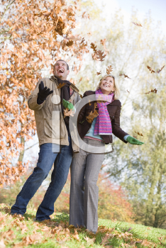 Royalty Free Photo of a Couple Playing in the Leaves