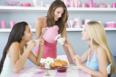 Royalty Free Photo of a Woman Serving Tea to Two Other Women