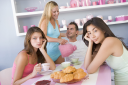 Royalty Free Photo of Women Looking Upset and Another Woman Pouring Tea for a Guy