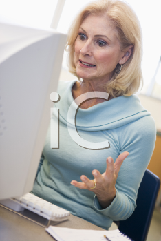 Royalty Free Photo of a Woman Looking Frustrated in Front of a Computer