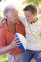 Royalty Free Photo of a Grandson and Grandfather With a Football
